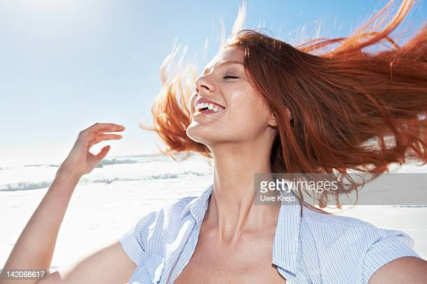 Young woman shaking head, outdoors