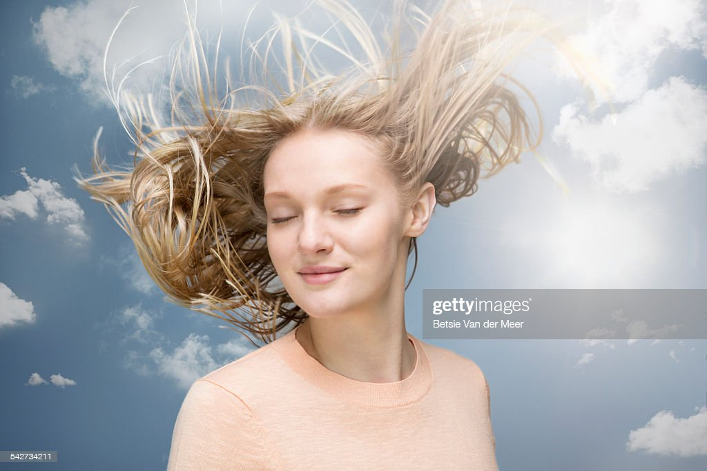 Young woman shaking her hair in wind : Stock Photo