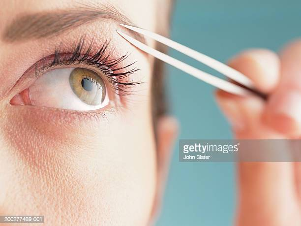 Young woman shaping eyebrow with tweezers, close-up of eye