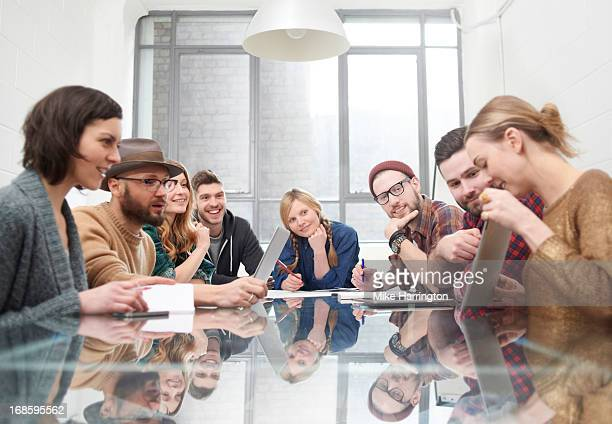 Young woman sharing ideas on ipad in meeting