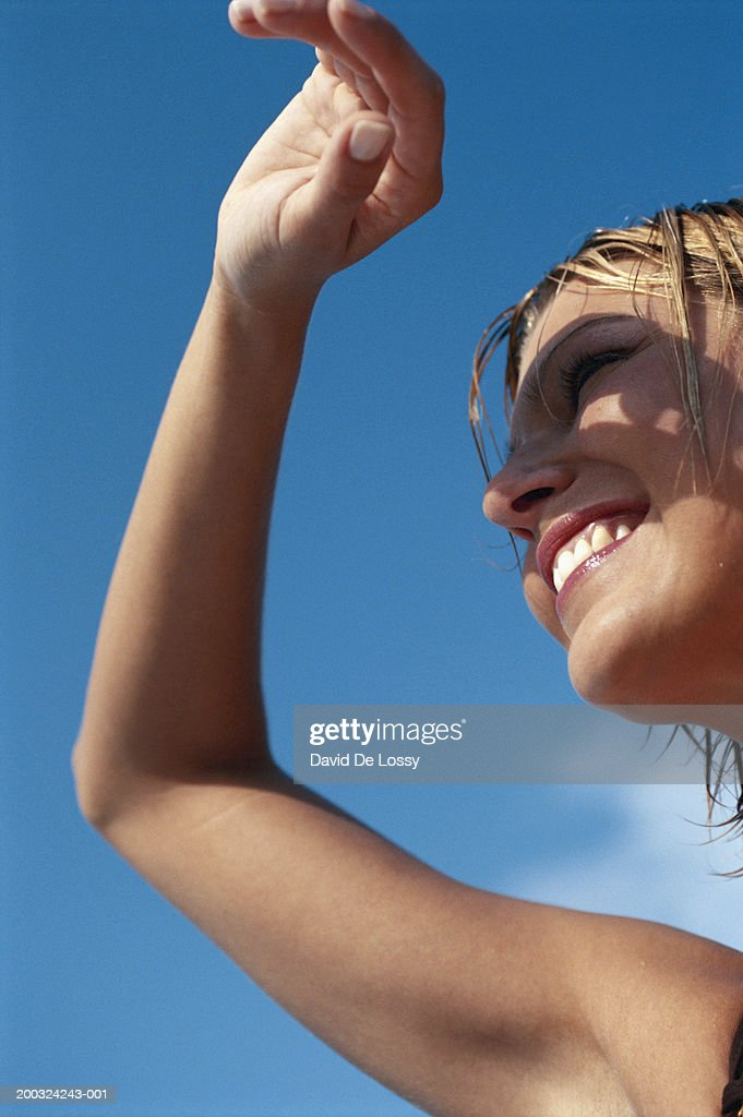Young woman shielding eyes, smiling, low angle view : Stock Photo