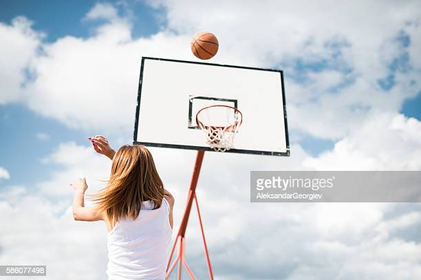 Young Woman Shooting at Basket on Outdoor Court