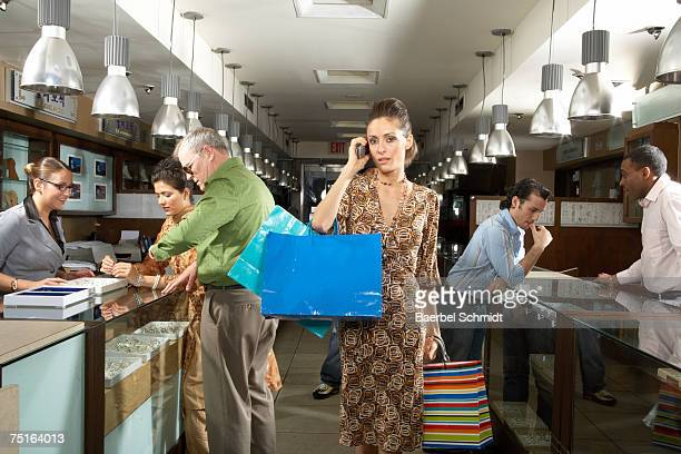 Young woman shopping and using mobile phone in department store