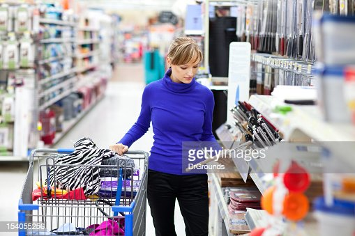 Young woman shopping at store checking label on product