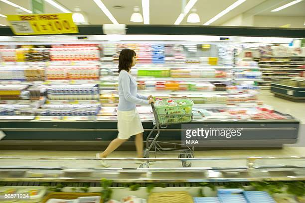 Young woman shopping at supermarket, blurred motion