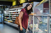 Mature woman standing at supermarket and buying salad. Young woman choosing fresh food from a counter of super market. Latin mid woman looking at take away food in grocery shop.