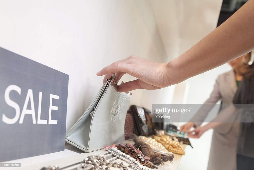 Young woman shopping for accessories at store, close-up