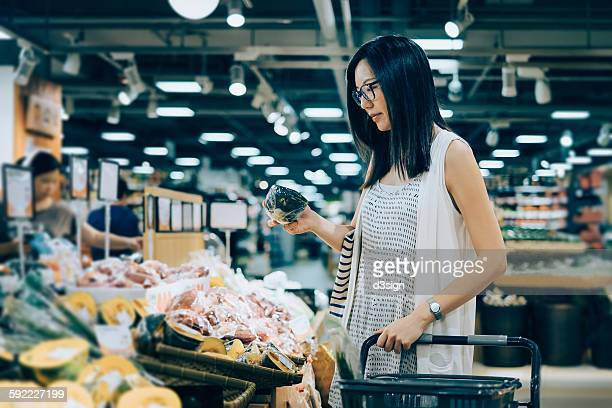 Young woman shopping for produces in grocery store