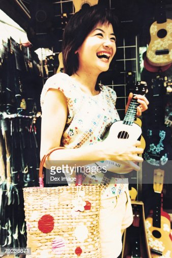Young woman shopping for Ukelele : Stock Photo