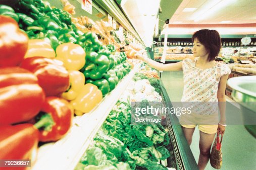 Young woman shopping for vegetables in fruit store : Stock Photo