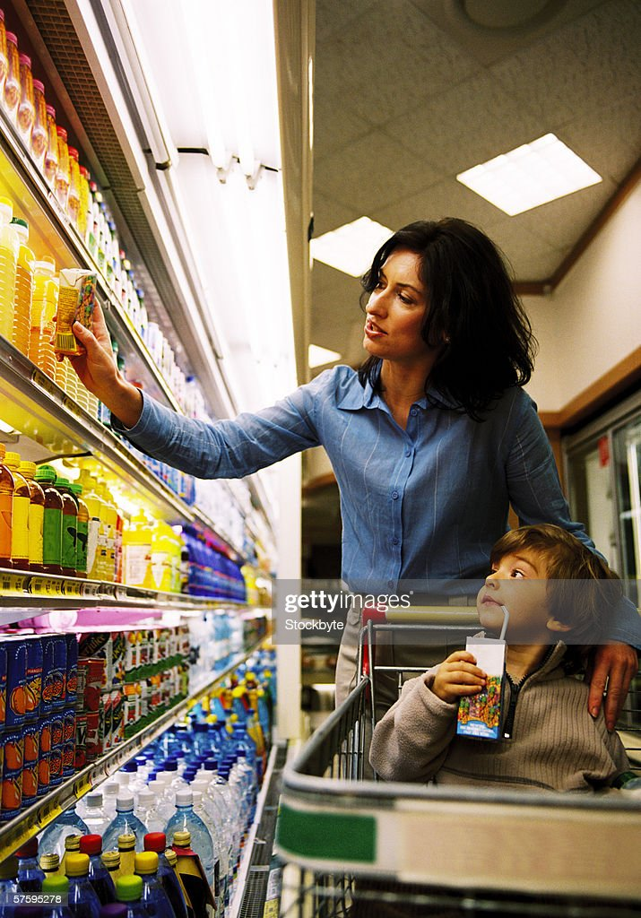 Young woman shopping in a supermarket looking at juices on the shelf : Stock Photo