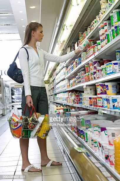 Young woman shopping in supermarket, holding basket, checking product