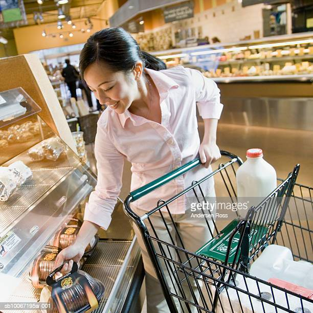 Young woman shopping in supermarket, smiling