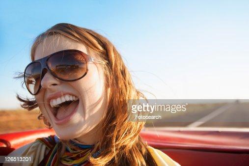 Young woman shouting in convertible