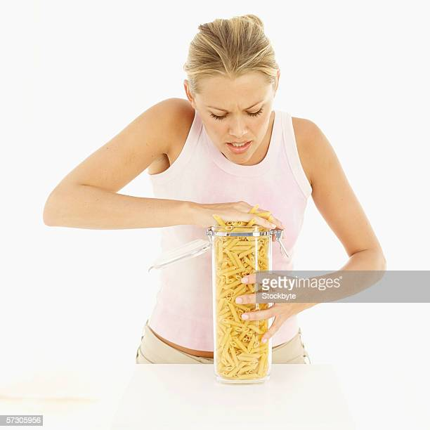 Young woman shoving uncooked pasta into jar