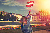 Young woman showing austrian flag in park outdoor vintage