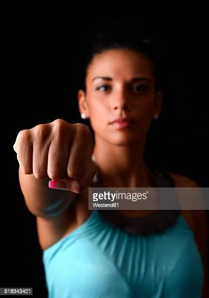 Young woman showing fist in front of black background