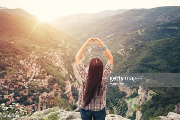 Young woman showing heart-shaped symbol