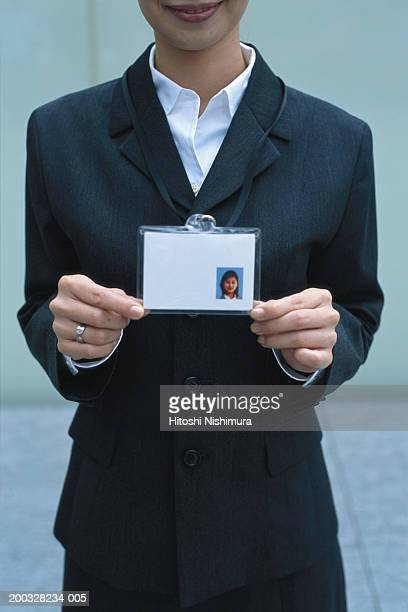 Young woman showing ID card, smiling, close up