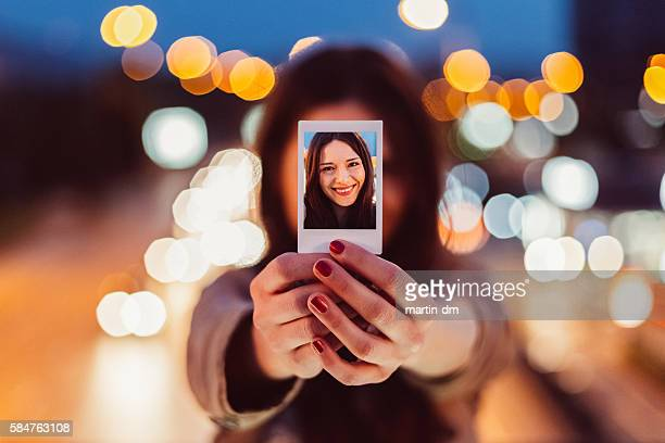 Young woman showing instant selfie
