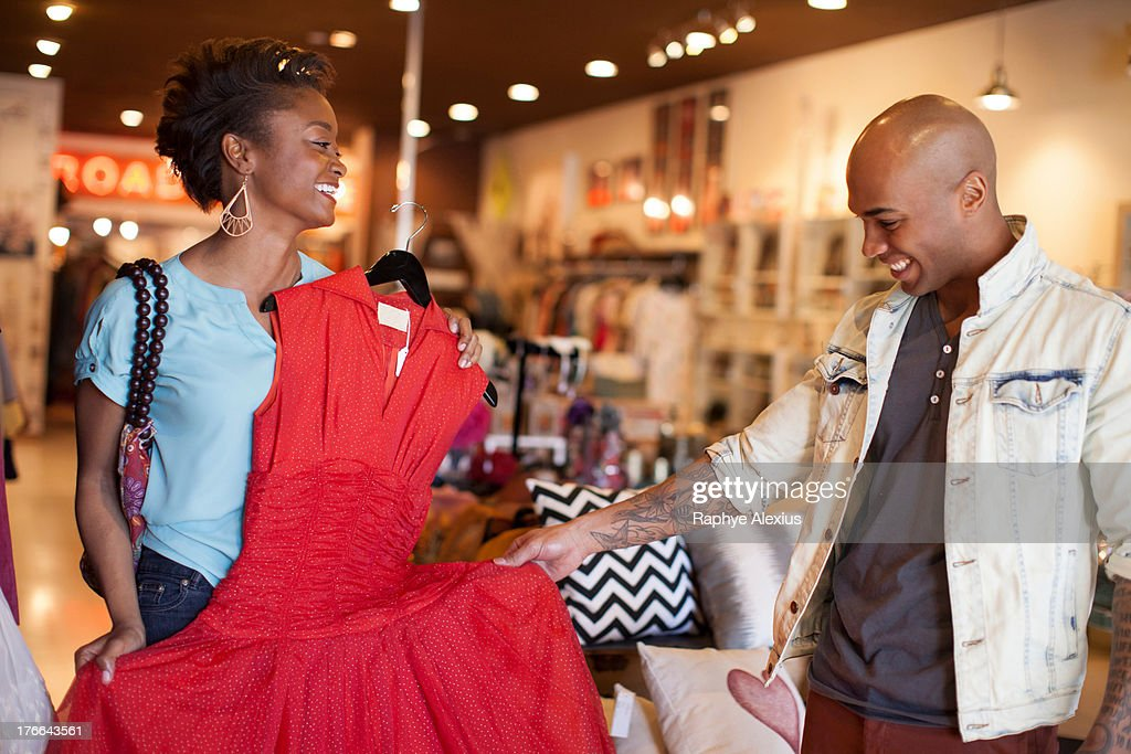 Young woman showing man red vintage dress : Stock Photo
