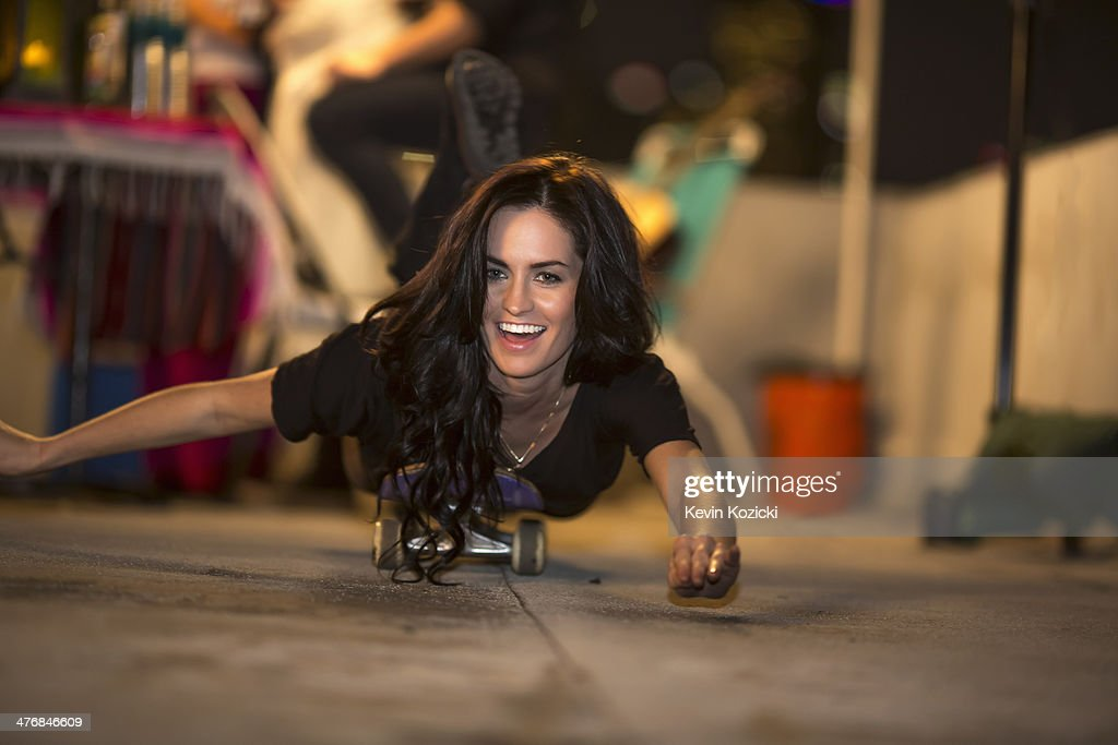 Young woman showing off on skateboard at rooftop party