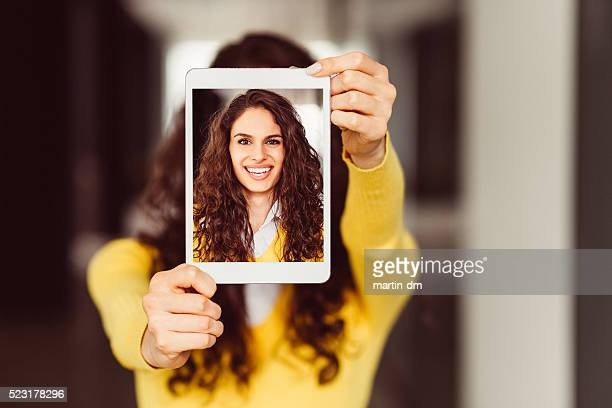 Young woman showing selfie on tablet pc