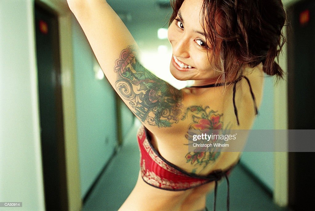 Young woman showing tattoos on arm and back in hotel hallway : Stock Photo