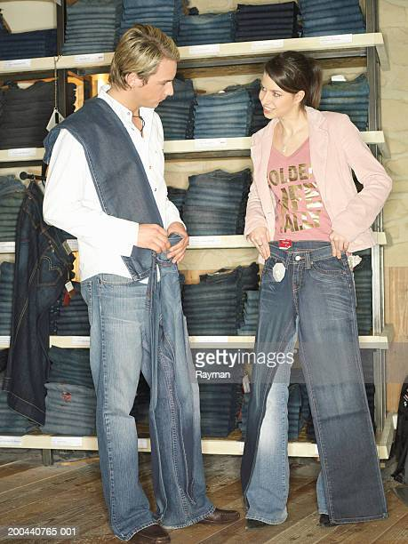 Young woman showing young man jeans in shop, smiling