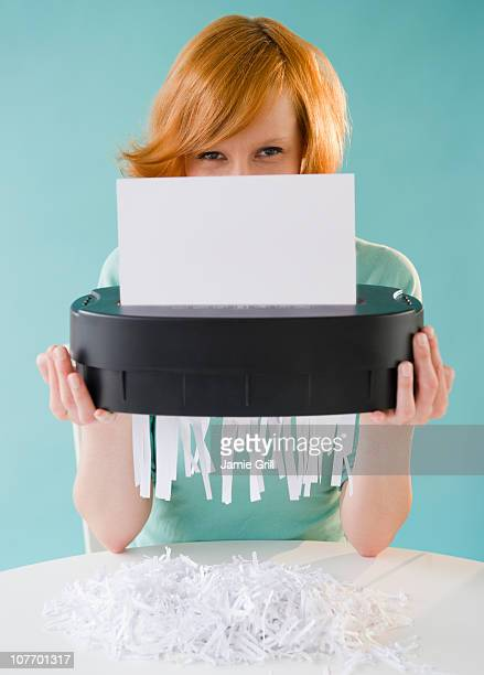 Young woman shredding paper