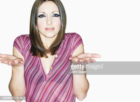 Young woman shrugging shoulders, close-up, portrait : Stockfoto