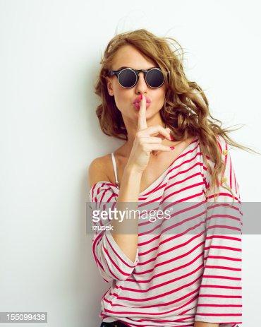 Young woman shushing