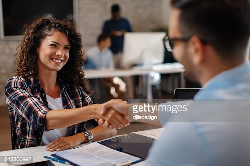 Young woman signing contracts and handshake with a manager : Stock Photo