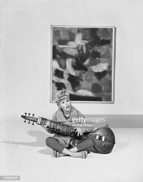 Young woman singing and playing sitar, portrait