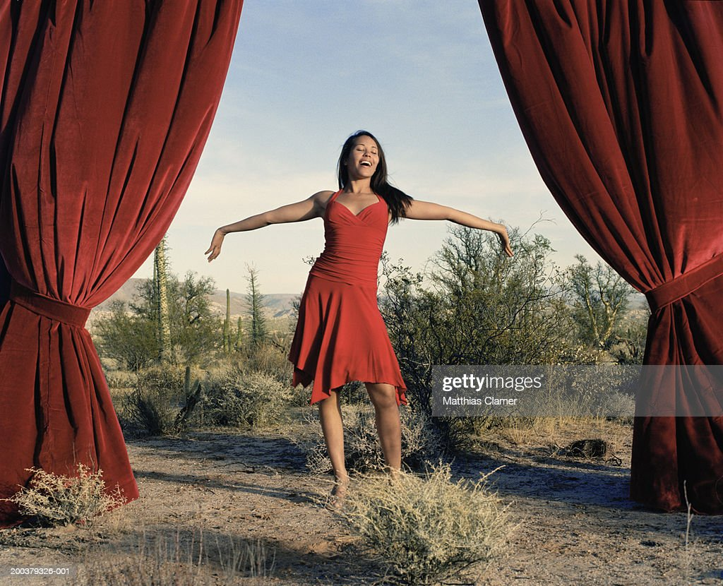 Young woman singing between curtain in desert : Stock Photo