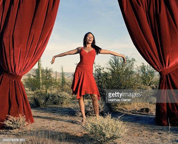 Young woman singing between curtain in desert