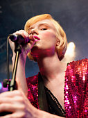 Young Woman Singing in Concert on stage, low angle view, close up