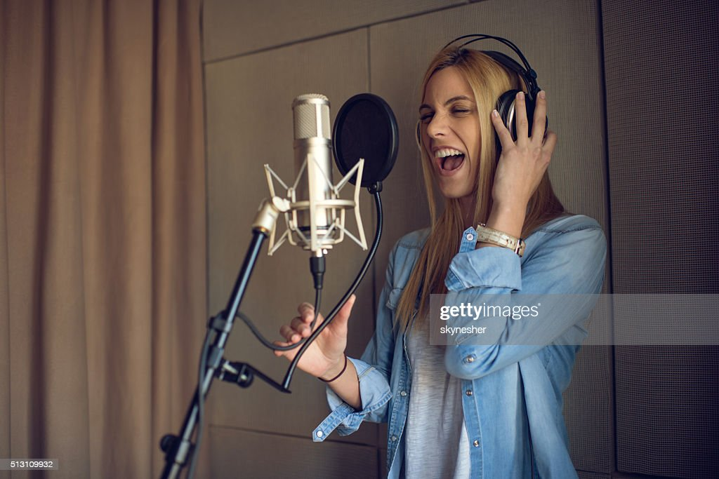 Young woman singing in recording studio.