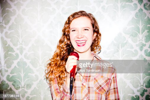 Young woman singing into a microphone : Stock Photo
