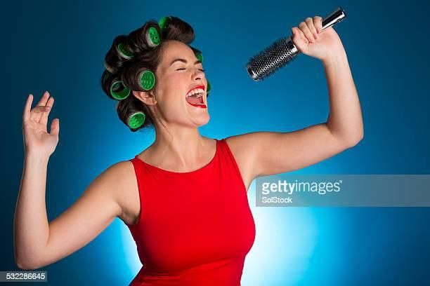 Jeune femme chantant à se brosser les cheveux