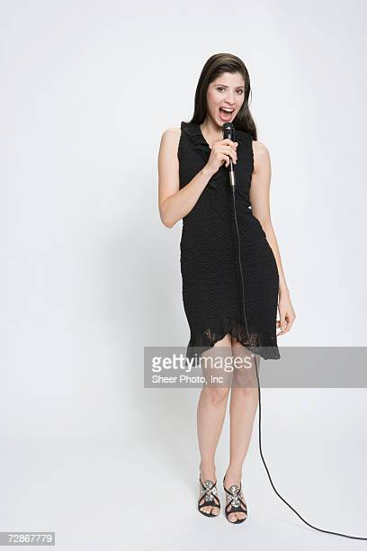 Young woman singing into microphone, portrait
