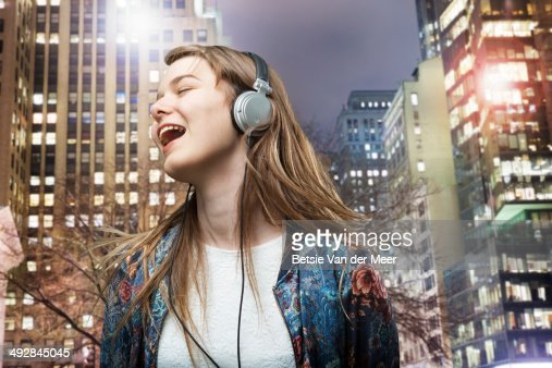 young woman singing to music at night in city. : Stock Photo