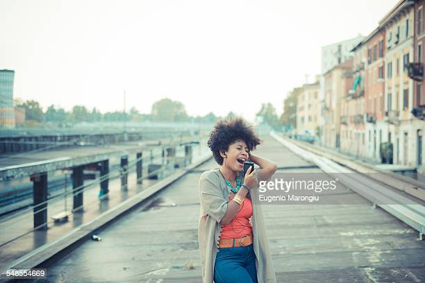 Young woman singing to music from smartphone in city industrial area
