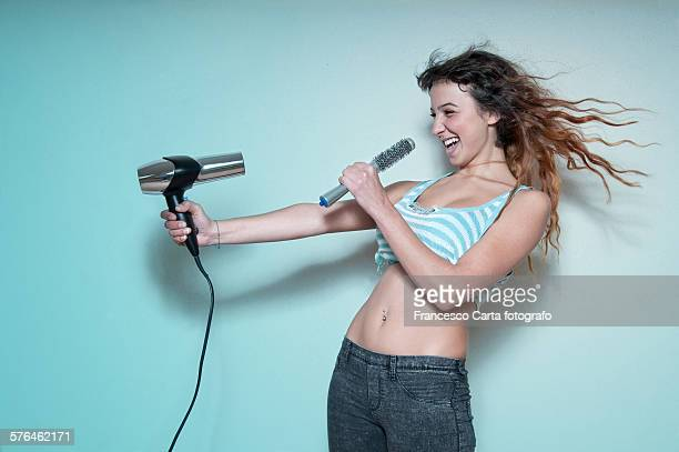 Young woman singing while drying her hair
