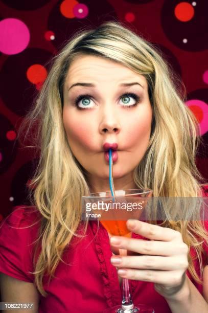 Jeune femme en sirotant un Cocktail auprès de paille