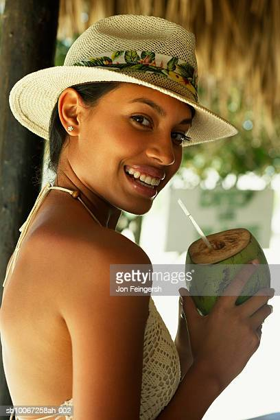 Young woman sipping coconut with straw, smiling, portrait