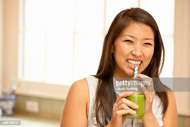 Young woman sipping green smoothie