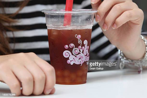 A young woman sips bubble tea outside a bubble tea cafe on August 22 2012 in Berlin Germany Bubble tea which fuses Asian tea with milk or fruit...