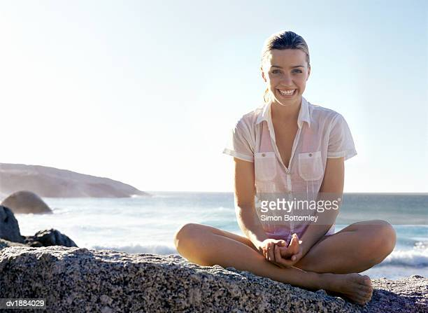 Young Woman Sits Cross-Legged Laughing on a Rock Near the Sea