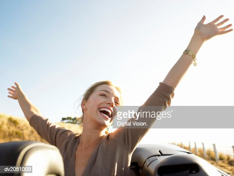 Young Woman Sits in the Back of a Convertible, Her Arms in the Air, Laughing With Joy